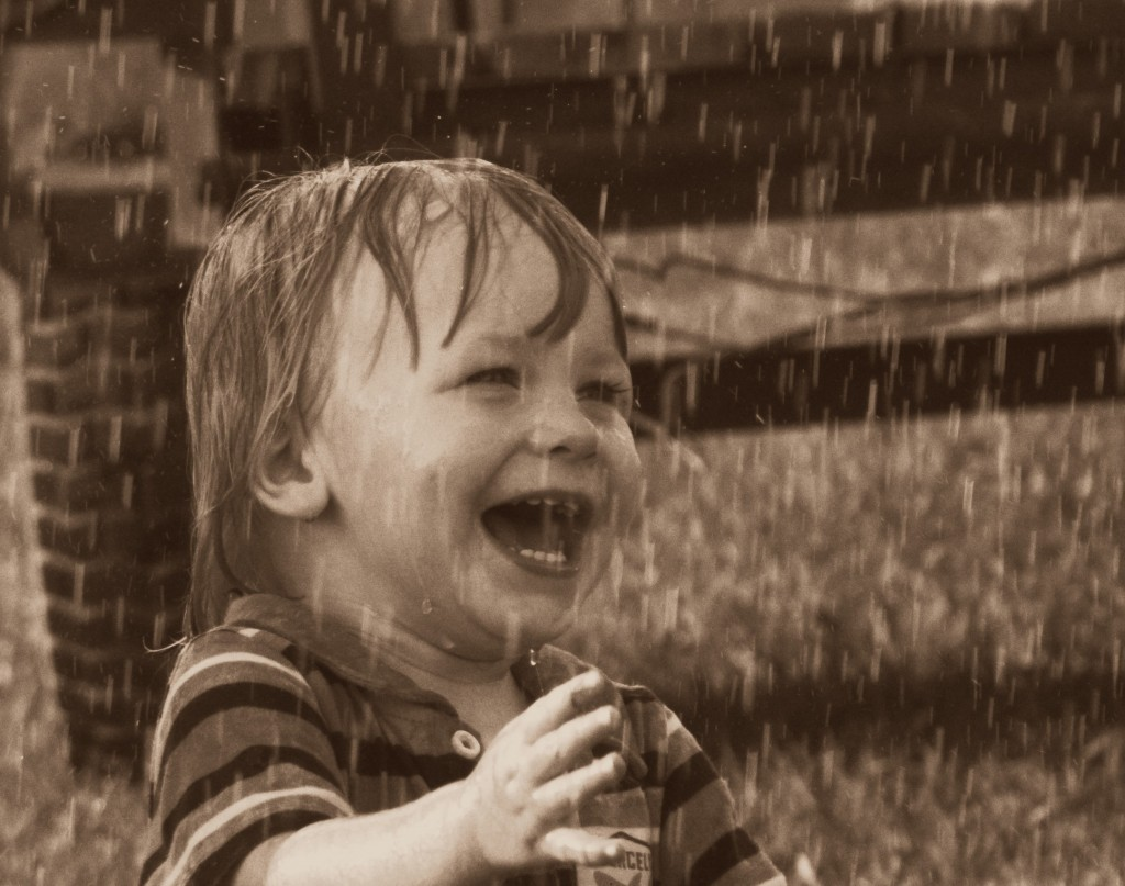 A toddler laughing in the rain.